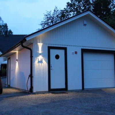Vitt garage med trevlig fasadbelysning